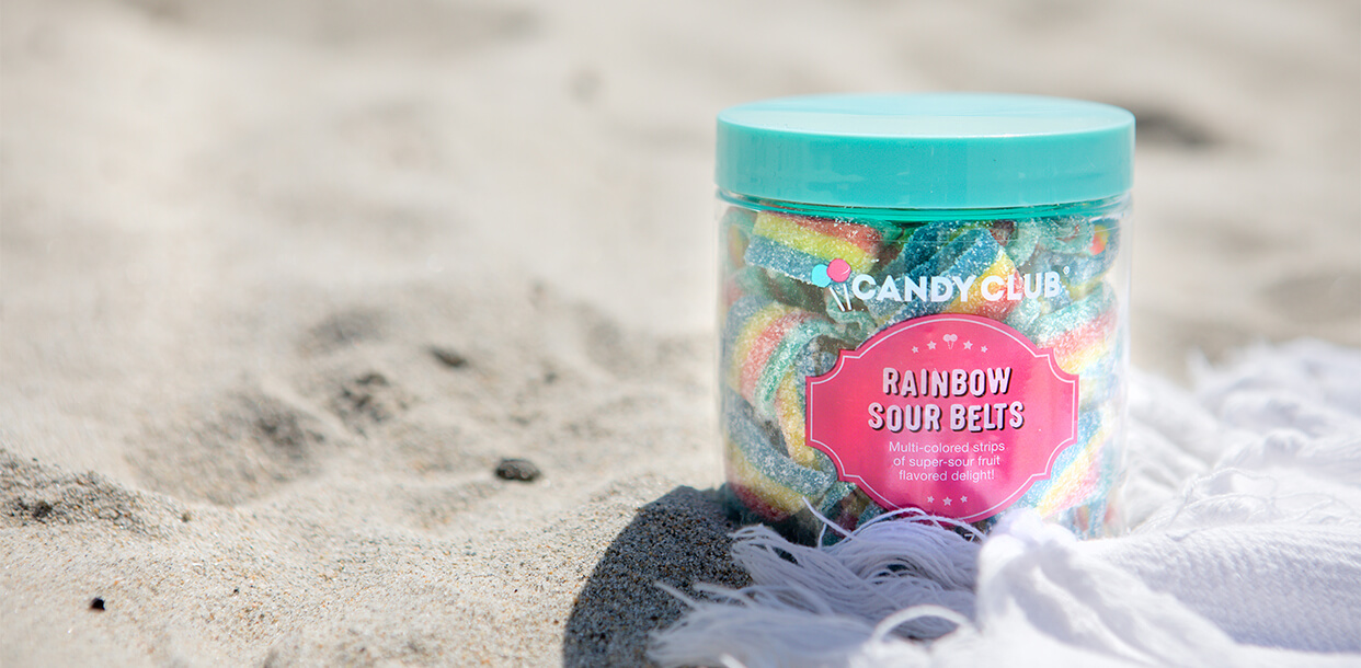 A premium cup of Candy Club Rainbow Sour Belts on the beach next to a towel on a bright summer day