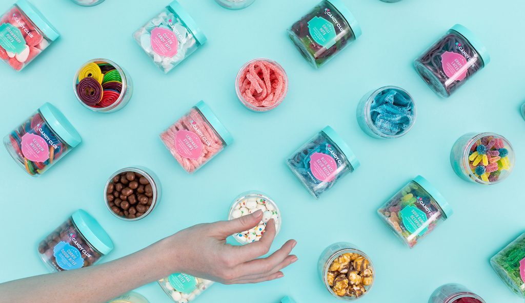 Overhead view of various Candy Club candies in jars with a hand grabbing a candy bite