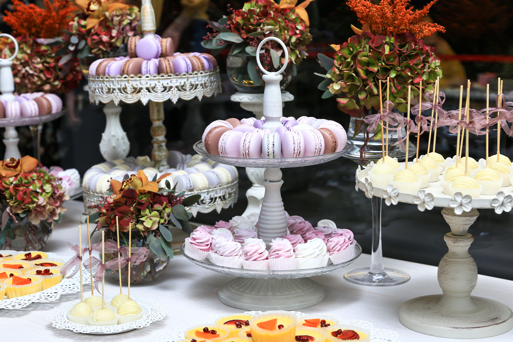 A dessert table with candy, macaroons, and other sweets in tones of lavender, pink, and white.