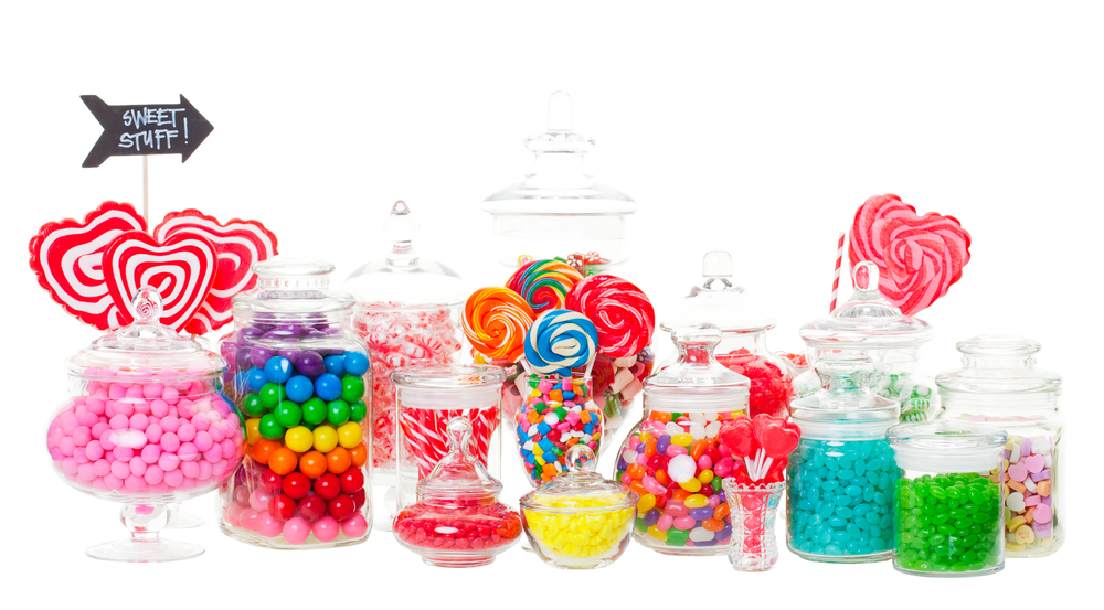 An assortment of candy in glass jars at a candy buffet