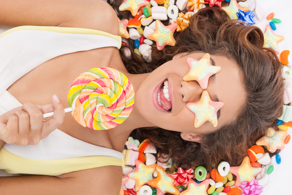 A woman sticking out her tongue while laying in candy with 2 starfish gummies covering her eyes while holding a rainbow lollipop.