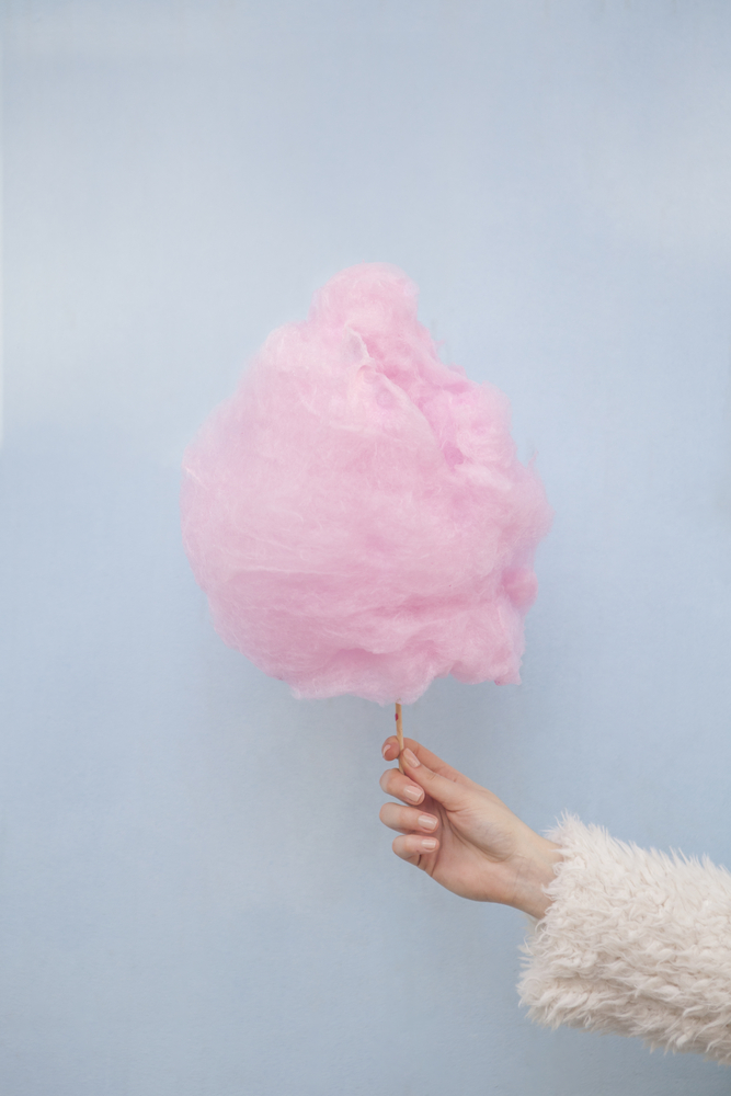 Fluffy pink cotton candy on a stick with a light blue background.