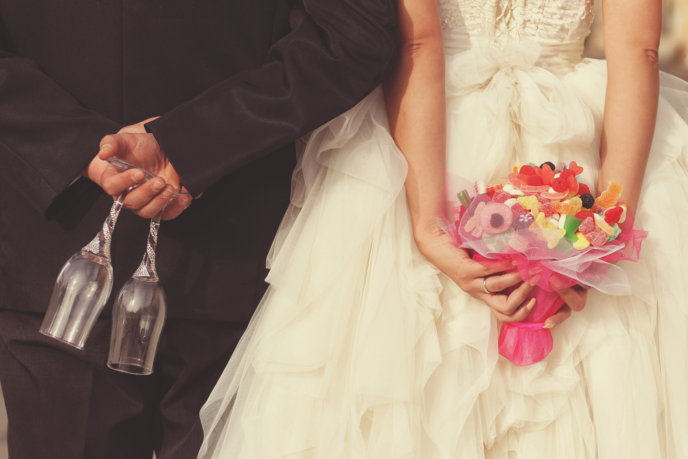 The backside of a bride and groom. The groom is holding 2 champagne glasses and the bride is holding a pink candy bouquet.