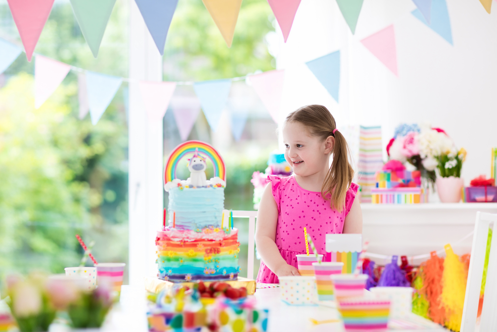 A girl happily looking at a rainbow frosted cake topped with a unicorn figurine at a birthday party.