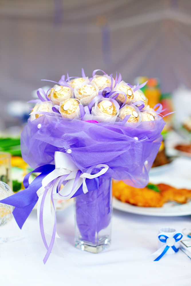 A candy bouquet made with gold-wrapped chocolate balls. Bouquet wrapped with purple lace.