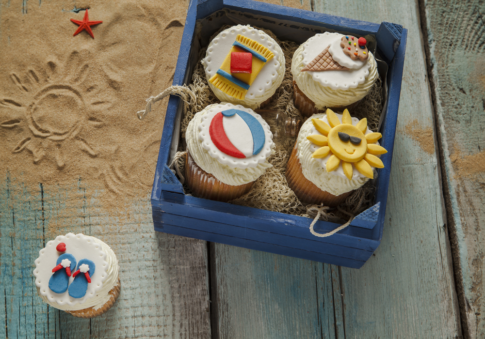 Cupcakes in a blue wooden box with summer/beach items on them - a sun, flip flops, ice cream cone, towel, and beach ball.