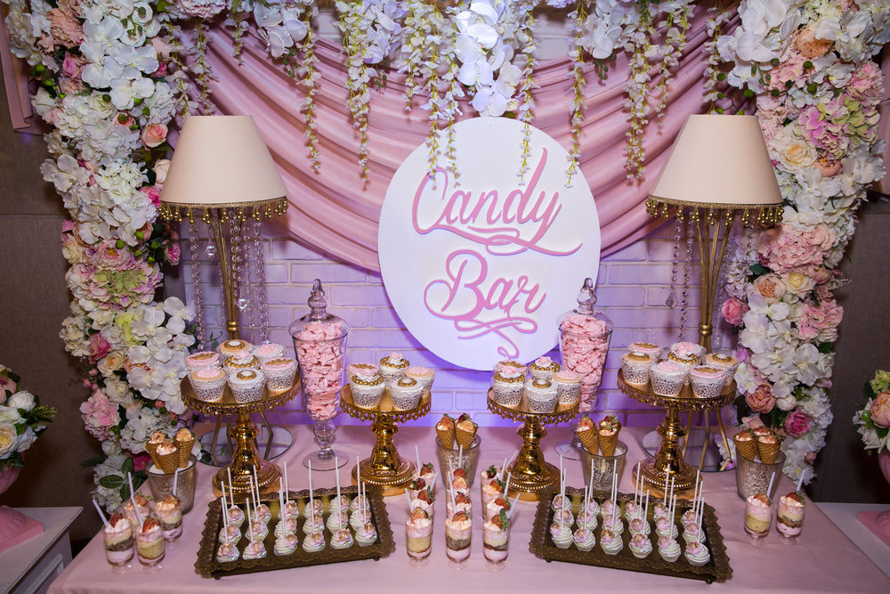 "A pink-themed ""candy bar"" filled with various candies and desserts."