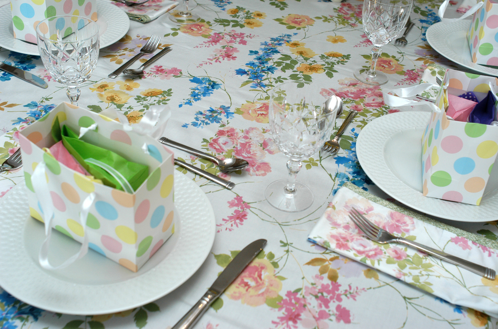 A table with a floral tablecloth and polkadot birthday bags on top of displayed plates.