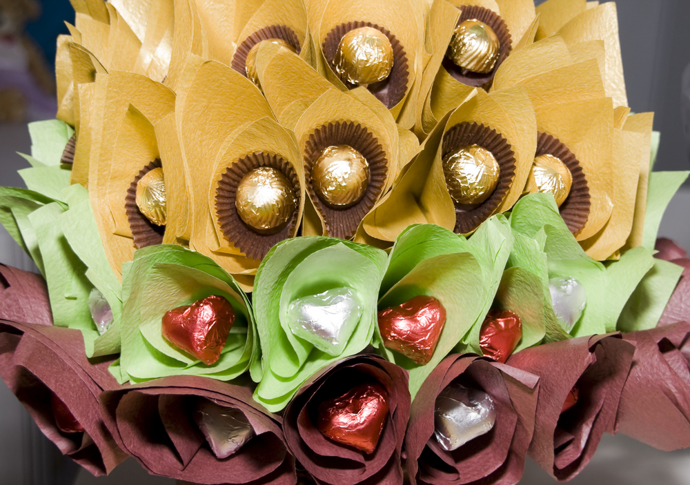 A candy bouquet of lined with yellow, green, and brown paper - centered with wrapped chocolates.