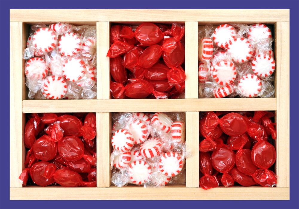 A wooden crate with six squares filled with wrapped peppermint candy.