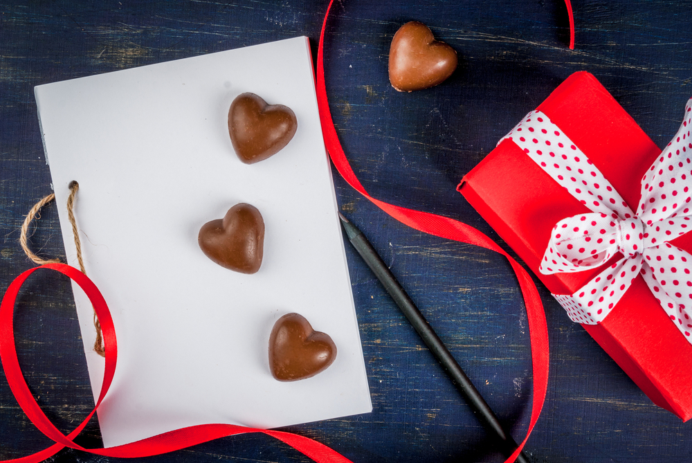 A white piece of paper with 3 chocolate hearts on top. A red ribbon is next to it with a red gift box.
