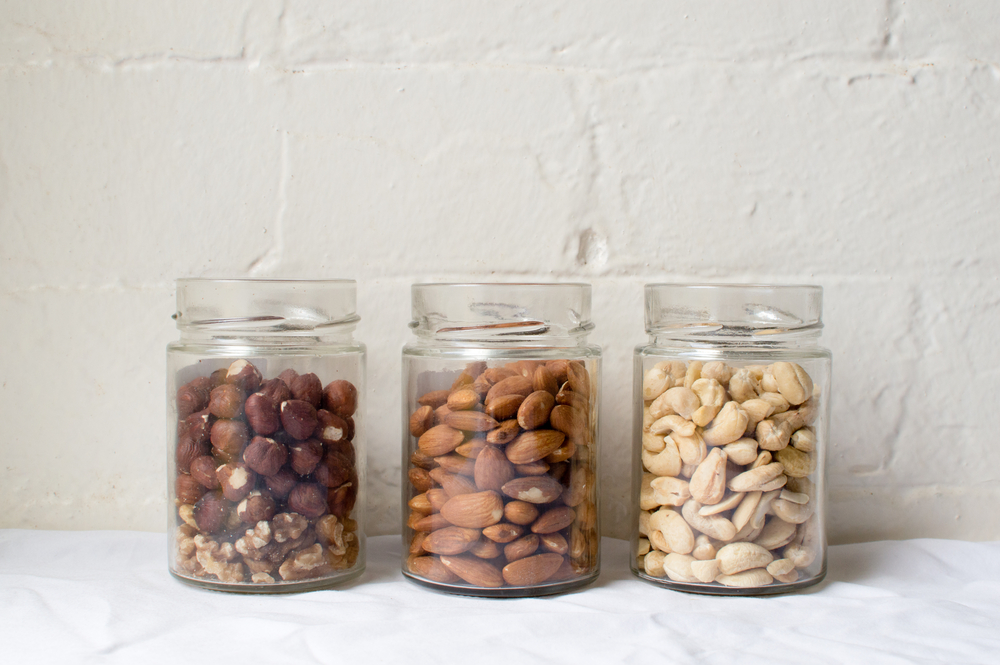 Three glass jars filled with macadamia nuts, almonds, and cashews.