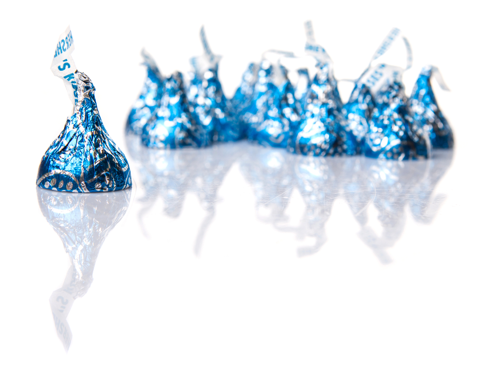 A blue Hershey's kiss in focus with a pile of Hershey's kisses in the background.