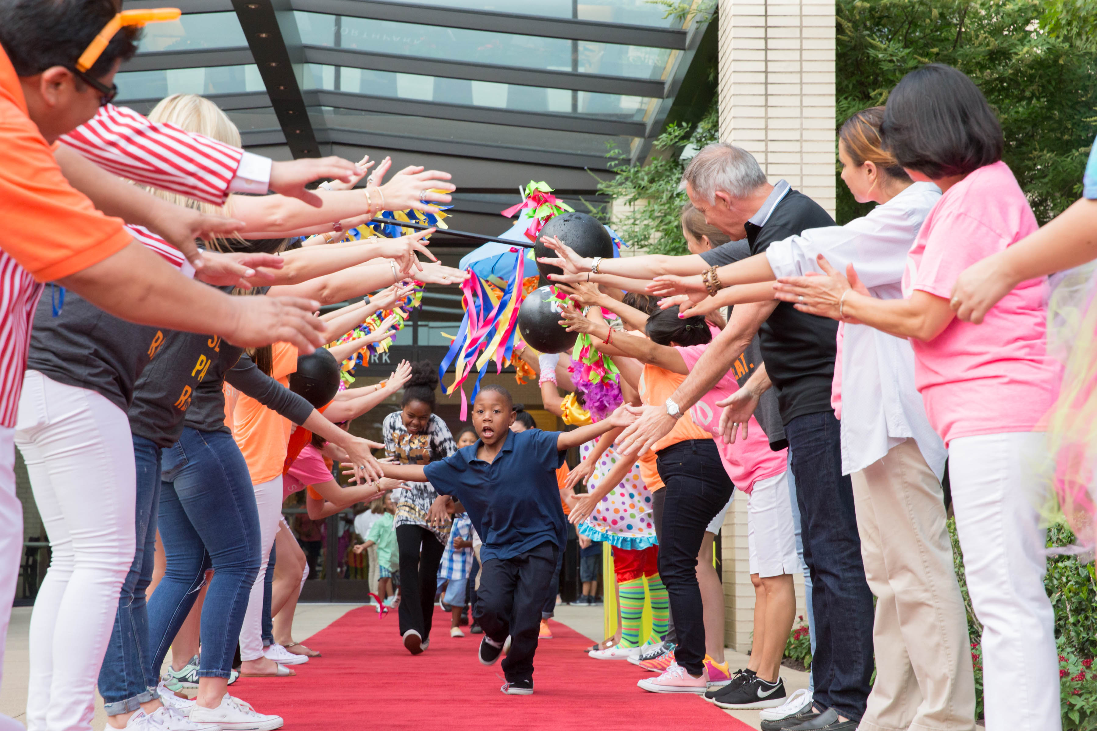 The Birthday Party Project - excited boy running down a red carpet of high fives and claps.