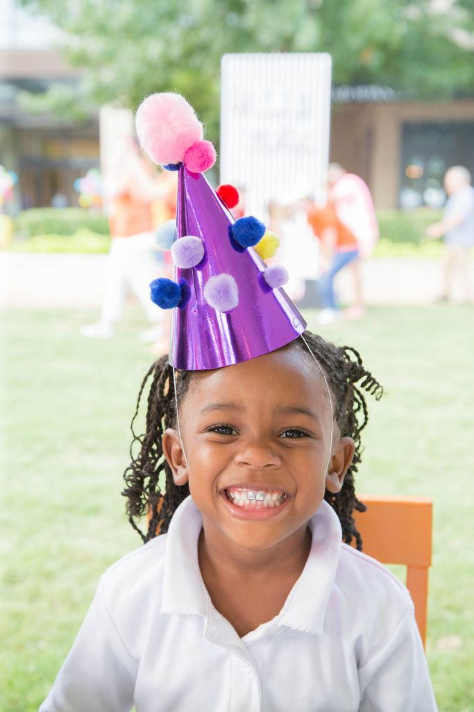 Young girl smiling while wearing a purple birthday hat with colorful pompom balls.
