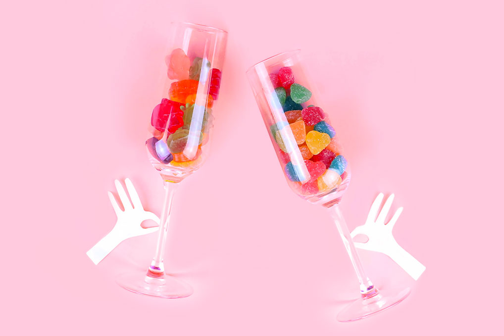 Two champagne glass full of colorful gummy candy with two paper hands grabbing them