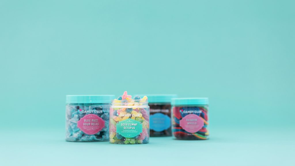 4 cups of Candy Club candies on a teal background
