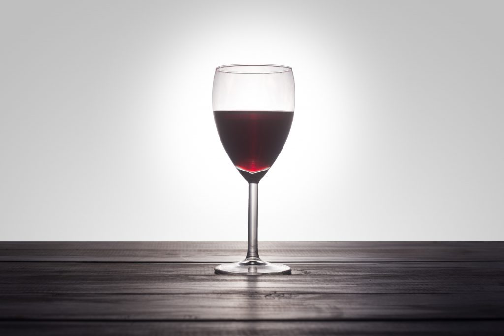 Glass of red wine on a dark wood table