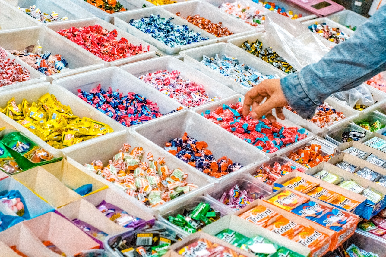 Assorted candy in square bins with a hand grabbing a candy